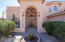 Manicured mature plantings and a grand covered front entry.