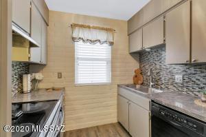 Kitchen with granite tile counters, tiled backsplash.