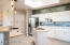Great natural light with skylights and tray ceiling, white cabinetry and ample counter space, 2 islands, breakfast bar seating and full wall backsplash.