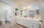 Located at the end of the bedroom hallway is the guest bath with double bowl vanity, tub/shower