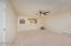 Neutral carpet, ceiling fan, walk in closet and window to the backyard