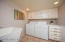 Laundry room completed with washer, dryer, built-in ironing board, storage cabinets and sink