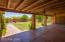 Deep covered patio looks out over the large yard with grass and fruit trees. Double doors at the end of the patio lead to the detached garage.