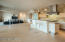 Elevated 3 stairs from living room, free flowing bar/island with glass counter surface, modern limestone series porcelain, custom designed suspension LED mobile chandelier multi-pendant sculpture of burnished steel/vintage platinum shades with acrylic filters adjustable for length & configuration.