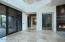 """Front entry leads to living room, stunning angular metal gas fireplace, 27' ceilings, 24"""" x 24"""" Sabbia Flooring"""