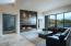 Massive angular fireplace with black glass.