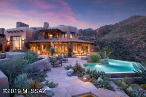 Located minutes from Canyon Ranch, this custom home on 49 acres is perched high on a high view lot between Ventana Canyon and Sabino Canyon.