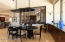 Sophisticated dining area with buffet and viewing window into elaborate wine room