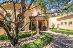 Nestled high on a premium lot in gated community, this private front elevation features custom rod iron and antique washed concrete design features with European style fountain. Convenient trash receptacle area located at bottom of driveway.
