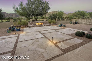 Custom backyard design. Low maintenance professional landscaping with stone pavers and custom gas fireplace.