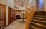 Formal Foyer with Decorative Travertine Flooring, Chandelier and Beautifully Crafted Normandy Staircase