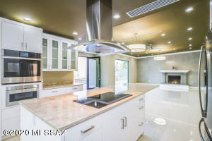 KITCHEN FEATURES HAND CRAFTED CABINETRY, INDUCTION STOVE TOP AND STAINLESS STEEL APPLIANCES