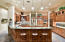 Chef's kitchen includes wood paneled bar.