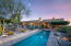 Resort-style living with many brick covered patios, lap pool and native desert plants.