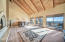 A massive great room with walls of windows, soring vaulted ceilings, and two-way fireplace