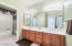 Shared guest bath for guest wing with dual vanities and shower/tub combo.
