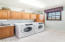 Spacious laundry room w/ sink and storage.