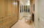 Just off the gentlemen's bath within the owner's suite is another generous closet with fabulous cabinetry and drawers, glass and wood full length clothing storage