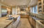 Kitchen includes an oversized Butler's pantry, column Subzero freezer, column Dacor refrigerator, 2 freezer drawers, 2 refrigerator drawers, 3 sinks, 6 burner gas stove, warming drawers, stainless and granite counters, and fantastic grand center island with rich butcher block counter