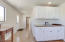 Full service kitchen includes sink, fridge, oven/stove, cabinets and counter space.