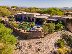 Situated on a corner lot and on just over one full acre, this custom burnt adobe home is located just West of the La Encantada outdoor mall.
