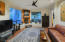 """Potential 3rd bedroom with a gas fireplace and built in """"bancos."""" Newer ceiling fan."""