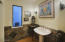 3rd bathroom with pedestal sink, sconces and tile wainscoting.