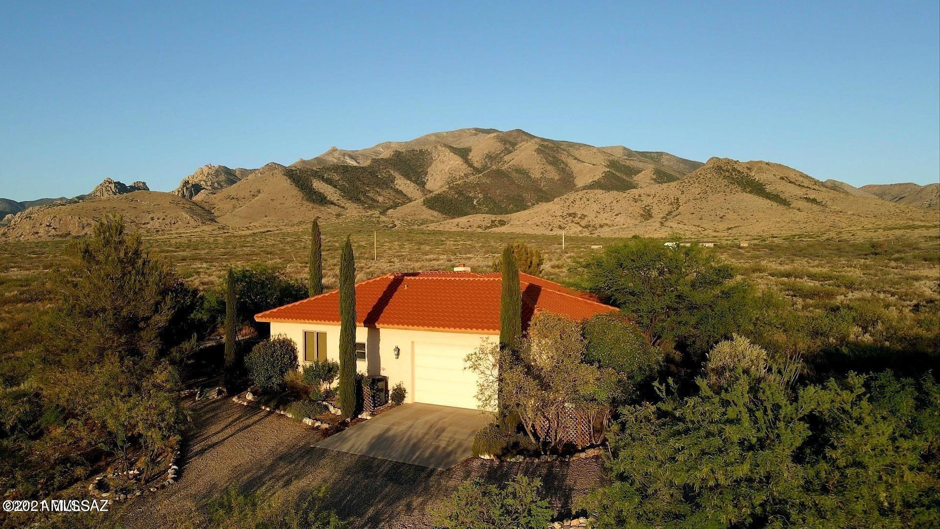Peaceful custom home surrounded by mountain views and nature.  This tranquil three bedroom home includes a full bathroom in each bedroom, plus a hall bath, extra storage, fireplace, recessed lighting,  AC, entertainment room, solid wood cabinets, covered patio, tile roof, dual pane windows, scored concrete floors, 2 stall barn, 2 car garage, garden area and so much more all on 10 acres!
