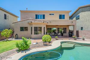 Lush backyard with patio and pool.
