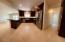 Great room and kitchen with view of hall leading to laundry room and bedroom.