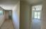 View into second bedroom with view to primary bedroom at end of hall.