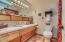 Hall bath with lovely original slanted front mid century cabinet, sliding doors and original tile.