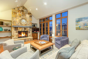 Enter the penthouse unit to the living space, fireplace and walls of glass with views of the San Sophia Ridge and ski area.