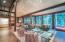 The large floor to ceiling glass almost brings the large aspen glen into the living room
