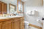 An upstairs hall bath has a single vanity and a step-in shower.