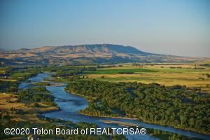 The Heart K Land and Cattle Co sellers Sept. 2020, have reduced the price from $32.5M to $24.95M by removing 90 ac of commercial. The ranch now is +/-1,976 acres of lush river bottom in the shadows of the Absaroka Beartooth mountains of SouthWest Montana. The famed blue ribbon Yellowstone River forms the north and western boundary for the ranch for some 5.5 miles which coupled with the abundance of whitetail deer, turkey, waterfowl, and upland birds solidify this ranch as a sportsman's dream. The ranch includes substantial surface water rights which it uses irrigate some +/-690 acres with 4 center-pivots. Historical carrying capacity is roughly 150 cow/calf pairs year-round with excess hay being sold.  There is a world class equine event facility featuring a heated 148'x242' indoor arena. Also, there is a beautiful remodeled original farm home with luxury bunkhouse, managers homes and historic barn set on the banks of the Yellowstone River. The Yellowstone River pours out of Paradise Valley about 5 miles up river from the ranch and it's about 60 miles up river to Gardiner MT and the Roosevelt Arch entrance to Yellowstone National Park at Mammoth Hot Springs.