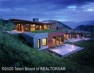 Set on 5.06 acres, discreetly tucked atop the ridge of Spring Creek, this property boasts unrivaled Grand Teton & Sleeping Indian views. Designed by Ward Blake Architects & offering 7,263 sq ft, 5 br, 6.5 ba, this exquisite home features a clean, contemporary design, with discreet, yet dramatic detail. Maple accents add warmth & softness to the interior design. Thoughtfully planned, the views & light are natural works of art that adorn every room. A water feature beckons you to enjoy the breathtaking setting & scenery. Enjoy mesmerizing 360 views from the main living spaces. Highlights include Viking appliances, a double-sided fireplace showcasing custom hammered steel artistry & bonus rooms fit for a gym, office, or extra bedroom. Enjoy Spring Creek Ranch amenities & proximity to Jackson