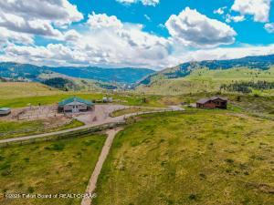 Looking for Beautiful Views, Privacy, USFS access, Equestrian Facilities and a Custom Home, only 20 minutes from Town? One of a kind views of the Snake River and Snake River Valley from this 35+ acre Horse Property. From large windows, enjoy views of valley from Hog Island to Wilson. Watch fishermen and rafters floating by on the Snake River, 400 feet below and marvel at the fall colors of Munger Mountain. From the property there is access to limitless miles of National Forest and Wilderness trails. This is one of only 7 homes on the 480 acres that make up the Porcupine Creek Ranch ISD. The 3 bed/2 bath home has rustic details including barn-wood, large log poles and beams, rough-sawn cedar, alder wood floors, chiseled edge marble countertops, a large elk antler chandelier and much more.