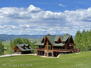 Your search for the perfect mountain retreat is at the end of the road where this family lodge on 44 acres overlooks scenic Star Valley and abuts National Forest. The Kuhns Bros log home features warm and inviting gathering and living spaces including a great room with a towering stone fireplace, rough-sawn barnwood flooring and large windows that provide abundant light and panoramic views. A detached 2-car garage with finished storage could be converted into a guesthouse. The country kitchen and dining room has on open design that extends to a large wrap-around Trex composite deck. Kitchen features include a 1920s antique stove with gas cooktop and 3 electric ovens, two sinks, granite countertops, alder cabinets, red spruce breakfast bar, self-closing drawers and a large walk-in pantry Also on the main level is an office that could serve as a sixth bedroom, and a spacious family room, which also opens to covered decks on both the west and east side of the home. More than 1,300 square feet of decking surrounds the house on three sides, with a large patio off the ground floor living area.  Offered with high quality furnishings and finishes. Hubbardton Forge lighting throughout is powered by Leviton Integrated Networks. Multiple fans help distribute heat in the winter, cool in the summer. A Lennox furnace heats the lower and main levels with cove heating in the upper level bedrooms. All bathroom floors are heated. The home also includes three wood-burning fireplaces - two inside the home that are equipped with blowers and a third outdoor fireplace.   A detached 2-car garage, in addition to the 2-car attached garage, provides plenty of room for all your mountain toys and vehicles, as well as finished space on the upper level that easily could be converted to a guesthouse.   The gently rolling land is comprised of four separately deeded lots totaling 44.5 acres that abut National Forest to the east. Adventure is out your door, as well as via numerous access points to pu