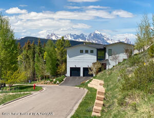 Bordering National Forest, this mountain modern home designed by local architect Brad Hoyt was completed in 2016. The oversized 0.47-acre parcel sits elevated above the valley floor offering views to the Teton Range. Views south capture vistas of Snow King and Cache Creek. The 3,027 sq.ft. floor plan features 3 bedrooms and 3.5 baths, including a generous master suite with office. A bright and airy great room frames views of the Grand Teton. A well-appointed kitchen is anchored by a massive center island for gathering with friends and family. An attached 2-car garage of more than 600 sq.ft. affords ample storage. A bonus space off the garage could be used as a workshop, exercise room or home office, or finished off in the same style as the upstairs living space to create a fourth bedroom.