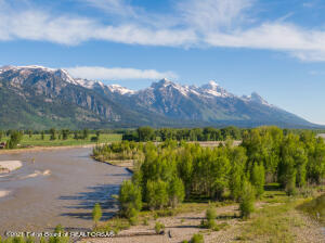 This pristine Snake River parcel is in a class of its own.  24.6 acres of unparalleled and undisturbed natural beauty, which must close simultaneously with lot 1 MLS 21-1906, is one of the last remaining undeveloped parcels on the Snake River in Jackson Hole . Upon stepping foot onto this property the discovery begins walking through the mature cottonwood and evergreen forests only to come to the banks and serenity of Linger Creek meandering along with the stunning Grand Teton views that will appear as you least expect it. Continuing forth the babbling creek and songbirds will take you further away and into this paradise, only to realize the local elk herd begins to gently scamper around.  You will eventually  find your way to  the Snake River, only to realize you are the only one present due to the private access this property provides. The sweeping Teton views from this vantage point are breathtaking as are the soaring birds of prey you will witness above. Now you have begun to imagine the creation of an estate second to none in the west. Endless recreational opportunities for the sportsman including world class fly fishing, hiking, biking, boating, swimming.  Bordered by Jackson Hole Land Trust conserved lands to the north and a 90 acre estate to the south protect this parcel to remain as the sanctuary you forever imagine. The proximity to the town of Jackson (11miles), the Jackson Hole Airport (7miles), Grand Teton National Park (10.5miles), Yellowstone National Park (51miles) and the Jackson Hole Mountain Resort (19 miles) complete this ideal Jackson Hole Retreat.