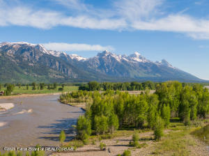 This pristine Snake River parcel is in a class of its own.  This 24.6 acres of unparalleled and undisturbed natural beauty, which must close simultaneously with lot 2 MLS 21-1907, is one of the last remaining undeveloped parcels on the Snake River in Jackson Hole. Upon stepping foot onto this property the discovery begins walking through the mature cottonwood and evergreen forests only to come to the banks and serenity of Linger Creek meandering along with the stunning Grand Teton views that will appear as you least expect it. Continuing forth the babbling creek and songbirds will take you further away and into this paradise, only to realize the local elk herd begins to gently scamper around.  You will eventually find your way to the Snake River, only to realize you are the only one present due to the private access this property provides. The sweeping Teton views from this vantage point are breathtaking as are the soaring birds of prey you will witness above. Now you have begun to imagine the creation of an estate second to none in the west. Endless recreational opportunities for the sportsman including world class fly fishing, hiking, biking, boating, swimming.  Bordered by Jackson Hole Land Trust conserved lands to the north and a 90 acre estate to the south protect this parcel to remain as the sanctuary you forever imagine. The proximity to the town of Jackson (11miles), the Jackson Hole Airport (7miles), Grand Teton National Park (10.5miles), Yellowstone National Park (51miles),  and the Jackson Hole Mountain Resort (19 miles) complete this ideal Jackson Hole Retreat.
