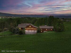 Enjoy the authentic feeling of a true Wyoming lifestyle property while taking in the views of the majestic Tetons and Grand Targhee ski area from almost every room in the house. This unique Alta property is nestled on 10 lush acres of meadow and aspen trees; overlooking a creek and a pond.  From the moment you enter this charming custom home, you will feel the quality of construction and attention to detail that has been integrated into the thoughtful design. The main home consists of 4 en-suite bedrooms, 4.5 baths with a large bonus room upstairs perfect for a media space or game room for family gatherings. Additionally, there is an office, a sunroom on the main level, and an artist studio workshop next to the two car attached garage. Graced by a charming covered porch off the kitchen to take in the fabulous views, the outdoor living spaces abound. There are French doors from the main bedroom suite, the dining area, and the living area which access this wonderful outdoor entertaining space, as well as French doors from the main bedroom to its own private covered deck on the south.   Directly next to the main house is the two bedroom guest house with vaulted ceilings and an additional attached garage(36' long with 12' x 12' ft overhead door)  perfect for a sprinter van or RV storage. The lovely courtyard connecting the two homes  offers a private outdoor space in a meticulously landscaped setting. Horses are welcomed on this 10 acre property and a barn can be added. The construction is a blend of log and frame with timber accents- tastefully melded, with  composite shingle roofing installed in 2007 on both structures. Other features include: 22k Guardian whisper quiet generator, whole house water filtration system, in floor propane heat throughout, 4 gas fireplaces, a woodfired cookstove, dual fuel range ovens (GE Monogram) and two jetted tubs. This is truly a one of a kind property in only a four lot neighborhood offering everything you are looking for.  Grab your 