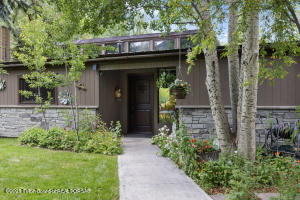 This hidden gem is nothing short of amazing. Located just 2 miles south of Town is your own little oasis. Recently remodeled and expanded, this beautiful home has thoughtful touches. Large windows in each room allow the natural light to flow through the home. Granite counter tops through-out, decorative barnwood paneling, durable Bamboo and concrete flooring.  There is excellent storage including an extra-large walk-in pantry off the kitchen and an exterior storage unit.  The front and back yards are not to be over looked. A meticulously manicured front yard and a large back yard offer a place for a range of outdoor activities.  Or relax under the pergola while enjoying the sunset from that patio.  There are 2 living areas, 4 comfortable bedrooms and 3 bathrooms set on a full acre.