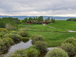 Enjoy a true Wyoming lifestyle property while taking in the views of the majestic Tetons & Grand Targhee. This unique Alta property is nestled on 10 lush acres of meadow & aspen trees, overlooking a creek & a pond. Thoughtfully designed, this custom home features quality construction, attention to detail, & exceptional views throughout. The main home consists of 4 en-suite bedrooms, 4.5 baths, with a large bonus room upstairs perfect for games & gatherings. Additionally, there is an office, a sunroom on the main level, & an artist's studio workshop next to the two-car attached garage. Outdoor entertaining spaces include a covered east-facing porch & courtyard. This property also boasts a 1-bedroom plus loft guest house that includes an attached RV garage with a 12' x 12' overhead door.