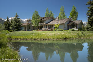 Framing exquisite views of the Teton Range, this 3 bed/3.5 bath home with 1 bed/1.5 bath guest house is ideally-located in the exclusive John Dodge area, less than 4 miles from JHMR and a few minutes' walk from the Snake River. Nestled on nearly 4 acres with native trees, a stream, pond and spacious deck, this abode is an ideal mountain retreat. Ample windows welcome boundless natural light and evoke a sense of immersion in the surrounding nature. The interior boasts a blend of contemporary and rustic ambiance with the warmth of wood finishes, 3 handcrafted river rock fireplaces, and double-height ceilings. The spacious kitchen offers all the refinements. Each bedroom enjoys an en-suite bathroom. The guest house shares stunning views and features a river rock fireplace, deck and garage.