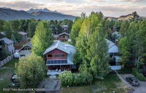 This owner-architect built home built in 2004, sits on a .17 acre (50'x150') homesite in the heart of East Jackson with views of Snow King mountain to the south and the Grand Teton to the north. Designed on 3 levels with 10-foot ceilings on the main level, the 2,333 sqft living space offers 3 bedrooms, 2.5 bathrooms, a home office, lower level bonus space--all with a flexible, open floor plan and abundant windows for natural light. Exterior space includes 3 sun-exposed decks and a covered balcony for outdoor lounging.  Building features include radiant floor heat, Jeldwen & Pozzi windows, natural gas boiler, wood composite beams, an HRV system, plus Bosch and Kitchen Aid appliances.  The home was designed with a focus on eco-friendly construction including five Photovoltaic solar panels installed by Creative Energies to offset the majority of the home's energy use.  Dual access from both the Redmond alley and Cache Creek Drive add to the easy enjoyment and flexibility of the property.  Zoning allows for 2 ARUs, one of which could be easily retrofitted in the lower level space, and another over a 2-car garage which could be added off of the alley.  This property is the perfect place for those keen on sustainability, convenience, and accessibility to the trails and downtown.
