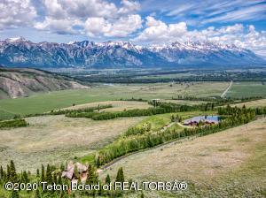 For those seeking the ultimate in privacy, while residing in the heart of Jackson Hole, this home gives you a direct mountain top view of the Grand Teton mountain range, the Jackson Hole Mountain Resort, and offers the ultimate seclusion in the exclusive Riva Ridge subdivision. A true family compound with a five bedroom main home, an apartment above the garage, and a private four bedroom guest house.  The main living room has floor to ceiling views of the private pond and mountain range.  Often you will see Wyoming's wildlife sip from the trout filled pond just steps from the front patio. Entertainment is at its finest with the private theater, game room, library, bar and a wine cellar to house the finest vintages. With 117 acres you'll have all the space you need to enjoy Jackson Hole.