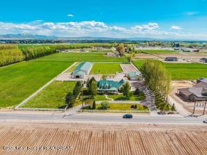 The premiere horse property in Southeast Idaho. . . . Imagine owning your own 5-acre elite level equestrian facility, with potential for additional acreage to the East. You're only within a few minutes of an airport, close freeway access, 25 minutes from both Idaho Falls and Pocatello for additional shopping and restaurants, and 2.5 hours from Salt Lake City, Jackson Hole, Sun Valley and Yellowstone National Park. The property features a state-of-the-art insulated indoor arena (200' X 60') complete with mirrors, professional lighting, sound and internet systems, a heated wash rack, finished tack room with a bathroom, and 6 custom horse stalls (16' X 14'') with outdoor runs and access to fenced lush pasture - all provide total comfort and functionality for your ideal equestrian experien The stately and expansive 6-bedroom, 4.5-bathroom home with almost 5000 square feet and a 516 square foot bonus room above the garage provide lavish accommodations for owners and guests. Primary en suite bedroom includes generous double walk-in closet and jetted tub in the bathroom. A very large pantry/food storage room on the lower level serves both the upstairs and downstairs kitchens. Mature grounds and landscaping surround the home, including willow, cottonwood, aspen, and evergreen trees as well an orchard of plum, peach, pear and a variety of apple trees. Shaded patio, porch and deck spaces, a fenced grass backyard, lawn with automatic sprinkler system produce a manicured beautiful and restorative oasis. The lower level of the main home could also serve as a full mother-in-law suite or guest quarters with a separate entrance and second kitchen area.   The 60' X 40' detached toy barn with over-sided bay doors easily fits, trucks, equipment, and at least two 5-horse trailers. There is also a separate 25' X 15' heated shop within for a year-round work station. The wide driveways and pull throughs make pulling in and out of the property, loading and unloading horses a breeze.  The p