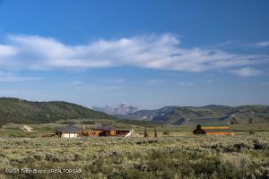 Truly a once-in-a-lifetime opportunity, this unique 110-acre property is located in the sweeping wilds of the Gros Ventre river valley. In addition to stunning views, three ponds, a haying operation, multiple barns and equine facilities, and a ranch manager's home, the property's heart is a custom built 7,486sq ft log home. Inspired by the ancestral designs of Navajo hogans, this one-of-a-kind 6 bed/5 bath home includes a spacious great room with an open concept kitchen, living, dining space -- anchored beneath a soaring, geometrically-distinctive ceiling crowned by a skylight, around a handcrafted river rock fireplace and log mantel. It also boasts a three-car garage, peacefully-secluded meditation room, ample storage, an office, spacious decks, an outdoor kitchen, and indoor greenhouse. A Location Apart There are few opportunities to own an expanse of 110 acres so near to the heart of Jackson Hole, while enjoying the peaceful seclusion of the untamed Wyoming wild. 38 miles from the Town Square, the Gunsight Ranch is a historic ranch balanced on a bench above the Wild & Scenic Gros Ventre River. Originally homesteaded in 1911, the property offers 360-degree views of the distinctive Gros Ventre mountains, the sweeping river valley below, and one of the area's most beautiful perspectives on the Cathedral Group of the Teton Mountain Range.  Situated in a swath of fragrant native sagebrush, the property is an inholding within the 3.4 million acres of the Bridger-Teton National Forest  which includes the pristine Gros Ventre Wilderness. Nearby, the free-flowing Gros Ventre River, which has been federally-designated as a Wild & Scenic waterway, is home to native cutthroat trout: a beautiful and robust fishery that offers hours of angling within minutes' walk or drive.   In addition to excellent fishing, this property's distinct location offers boundless choices for recreation year-round. Summertime includes millions of miles of trails for hiking, mountain biking, and hor